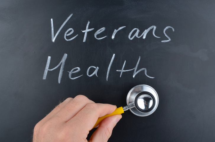 Veterans health handwritten on a blackboard in white chalk with a doctors hand holding a stethoscope.